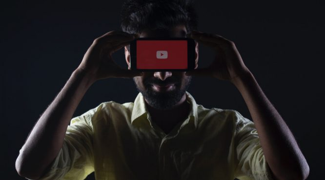 man holding phone with youtube logo