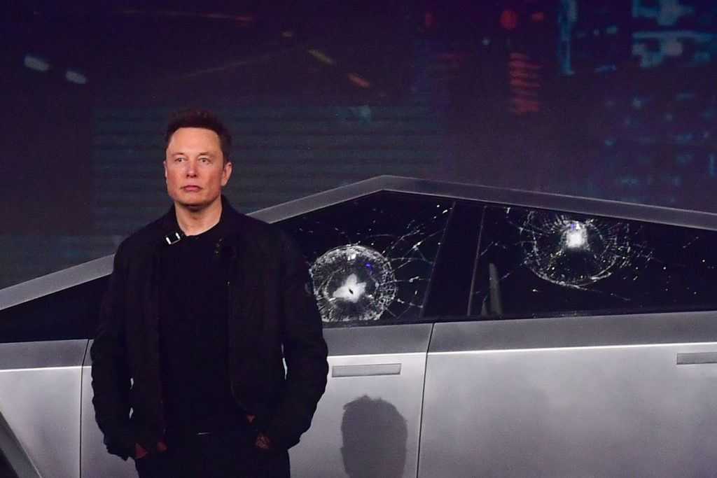 elon musk in front of the cybertruck with a broken window